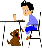 Boy and his dog. Boy feeding his dog underneath the table at dinner time Royalty Free Stock Photography