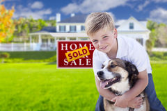 Boy and His Dog in Front of Sold Sign, House. Happy Young Boy and His Dog in Front of Sold For Sale Real Estate Sign and House Stock Images