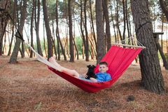Boy and his dog relaxing in hammock Royalty Free Stock Photo