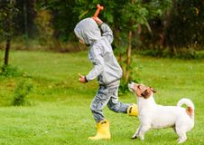 Kid boy wearing waterproof coat playing with dog under rain. Boy and his dog running at backyard under rain stock images
