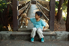 A boy and his dog. A boy sitting on a bridge petting his dog Royalty Free Stock Photos