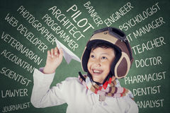 Boy with his dreams holds a paper plane. Little boy holding a paper plane in the class while wearing helmet with his dreams on the blackboard Royalty Free Stock Images