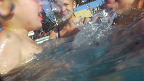 Boy and his family having fun in the pool stock footage