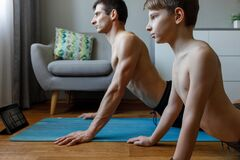 Boy with his father doing cobra yoga pose at home