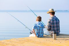 Boy and his father fishing togethe. R from a pier stock images