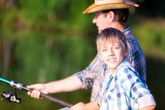 Boy and his father fishing togethe. R from a pier royalty free stock photo
