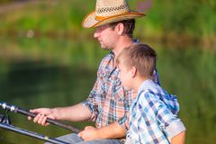 Boy and his father fishing togethe. R from a pier stock image