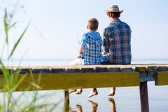 Boy and his father fishing togethe. R from a pier stock photos