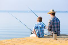 Boy and his father fishing togethe. R from a pier royalty free stock photos