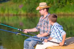 Boy and his father fishing togethe. R from a pier stock photo