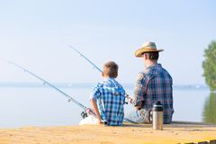 Boy and his father fishing togethe. R from a pier royalty free stock photography