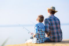 Boy and his father fishing togethe. R from a pier royalty free stock image