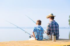 Boy and his father fishing togethe. R from a pier stock photography