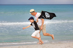 Boy and his father having fun on tropical beach. Cute little boy and his father having fun on tropical beach Stock Photos
