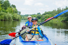 Boy with his father kayaking Royalty Free Stock Photo