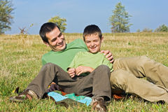 Boy and his father laying outside. Happy boy and his father smiling outside Royalty Free Stock Images