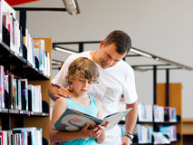 Boy and his father in library Royalty Free Stock Image
