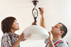 Boy and his father mounting ceiling lamp together. Child helping and learning while fastening the wire masking element royalty free stock photo