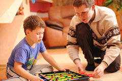 Boy and his father playing board soccer game at home Stock Image