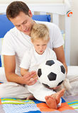Boy and his father playing with a soccer ball Royalty Free Stock Photography