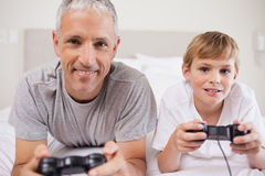 Boy and his father playing video games Stock Photos
