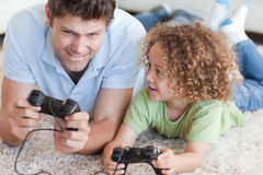 Boy and his father playing video games Stock Images