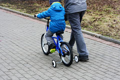 A boy with his father riding a Bicycle. Stock Photo