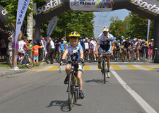 Boy with his father riding bicycles, competing for Road Grand Prix event, a high-speed circuit race in Ploiesti-Romania. PLOIESTI-BUCHAREST - JULY, 05: Boy with stock image