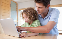 Boy and his father using a laptop. In a kitchen royalty free stock photography