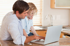 Boy and his father using a laptop together. In a kitchen stock photography