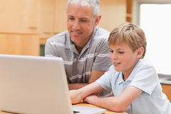 Boy and his father using a notebook Royalty Free Stock Image