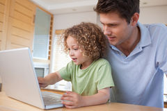 Boy and his father using a notebook Royalty Free Stock Photo