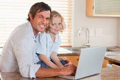 Boy and his father using a notebook together Stock Images