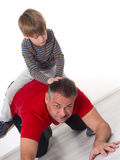 A boy on his fathers back, parenting can be diffic Royalty Free Stock Photo