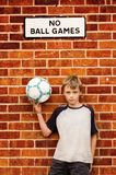 Boy and his football. A ten year old boy holding a football near a sign Stock Images