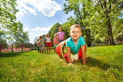 Boy and his friends crawling through the tube Stock Photo