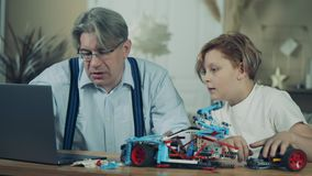 A boy and his granddad are assembling a toy car together