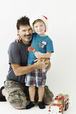 Boy and his grandfather on with Christmas candy. Grandpa with grandson on white background and white floor. grandfather sitting on  on his knees and his grandson Stock Images