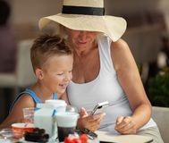 A lunch with granny. A boy and his grandmother in a wide brim hat having their lunch outdoor and watching a smartphone royalty free stock photography