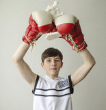 Boy with his hands raised in boxing gloves in a victory gesture with a figurine of a boxer Stock Photography