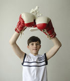 Boy with his hands raised in boxing gloves in a victory gesture with a figurine of a boxer Royalty Free Stock Photos