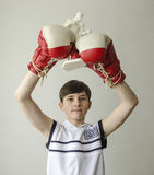 Boy with his hands raised in boxing gloves in a victory gesture with a figurine of a boxer Royalty Free Stock Photography