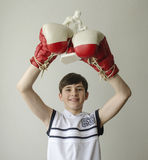 Boy with his hands raised in boxing gloves in a victory gesture with a figurine of a boxer Royalty Free Stock Image