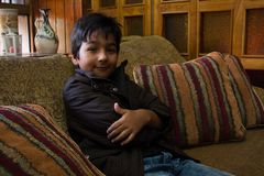 Boy in his house with brown jacket on a couch 2 Stock Photos