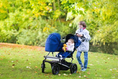 Boy with his little siblings in double hogger stroller Royalty Free Stock Photos