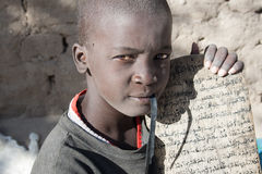 Boy and his manuscript in Arabic. TIMBUKTU, MALI - JANUARY 3, 2010: Boy showing his Arabic manuscript probably copied from the Koran on January 3, 2010, Timbuktu Stock Image