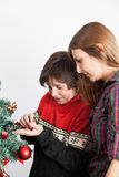 Boy with his mom decorating the christmas tree. Boy with his mom beside the christmas tree Royalty Free Stock Photo