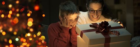 Boy and his mom opening a beautiful Christmas gift stock photos