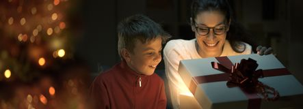 Boy and his mom opening a beautiful Christmas gift royalty free stock image