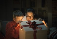 Boy and his mom opening a beautiful Christmas gift stock image